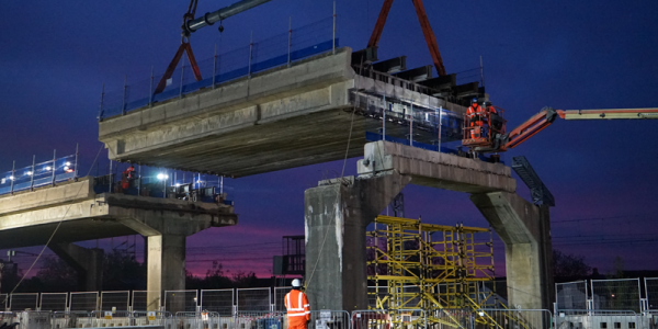 An image of a crane lifting a large slab of concrete at the Bletchley Flyover