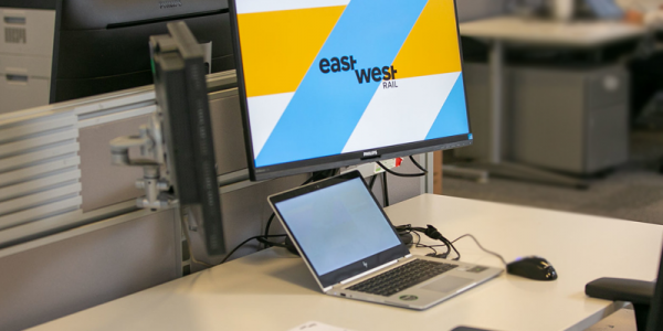 An image of a laptop screen with the words 'East West Rail' shown on screen via a screensaver