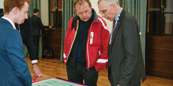 An image of SImon Blanchflower, CEO of East West Railway Company - looking at a map and engaging with a stakeholder at an event.